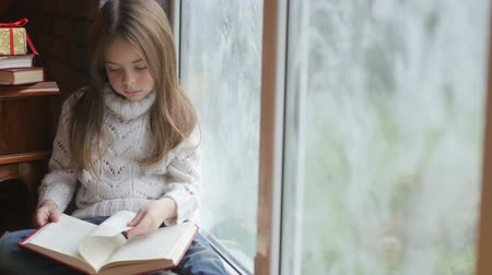 girl reading a book at home sitting on the windowsill
