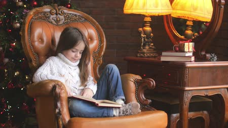 girl reading a book at home sitting in a chair