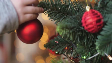 lose-up, childrens hands decorate the holiday tree, bright festive background