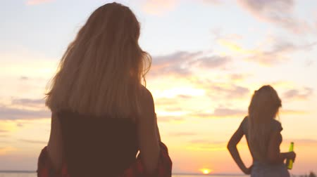 dinlenmek : A young girl enjoys a girlfriend on the beach. Silhouetted woman at sunset beach. Silhouettes at sunset.