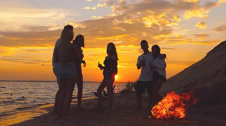 baví : Group of people at the beach near the bonfire. Slow motion.