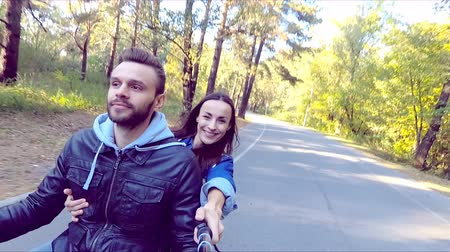 vara : Happy couple riding a scooter in the forest. Sunny beautiful day. Selfie-stick camera view.