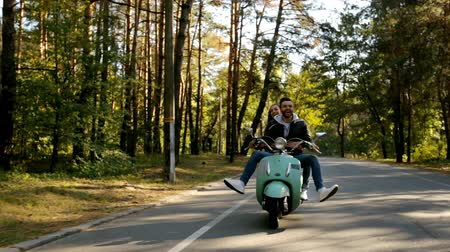 istantanea : Happy couple riding a scooter in the forest. Sunny beautiful day. Filmati Stock