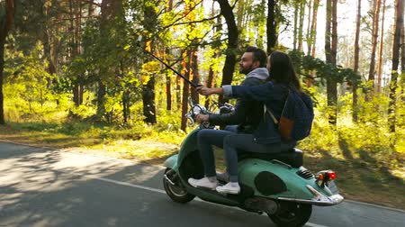 istantanea : Happy couple riding and taking selfie video on a scooter in the forest. Sunny beautiful day.