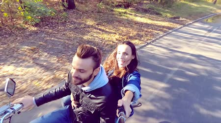 istantanea : Happy couple riding a scooter in the forest. Sunny beautiful day. Selfie-stick camera view. Slow motion.