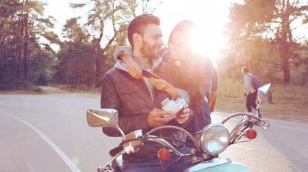 casal : Young couple sitting on the scooter and looking on the photo cards, which they just have done. Stock Footage