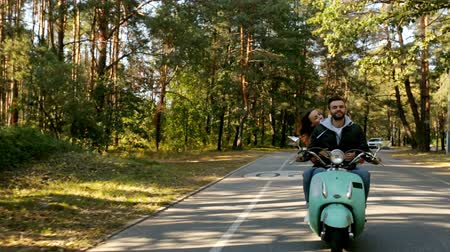 motorino : Happy couple riding a scooter in the forest. Sunny beautiful day. Filmati Stock