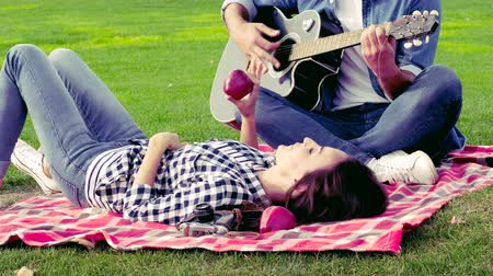 pléd : Happy couple in love having a good time on the green lawn. The guy plays the guitar.