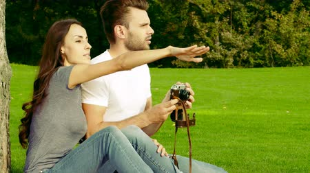 Happy couple taking pictures with an old camera on a green lawn.