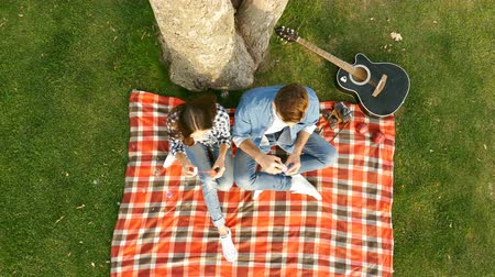 Happy couple blowing bubbles while sitting under a big tree on campus. Top view. Dostupné videozáznamy