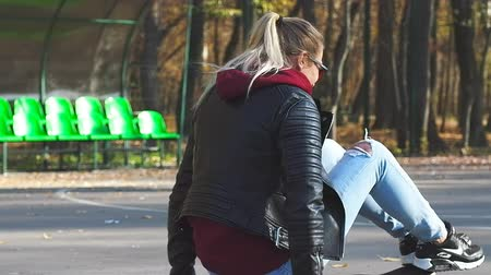 Lifestyle Caucasian blonde teen girl in jeans sitting on a longboard. Dostupné videozáznamy