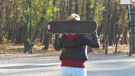 Beautiful girl goes with her board in her hands.