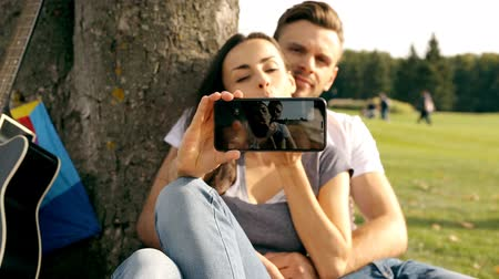 instante : Happy couple taking a picture of themselves with a smartphone on a green lawn.