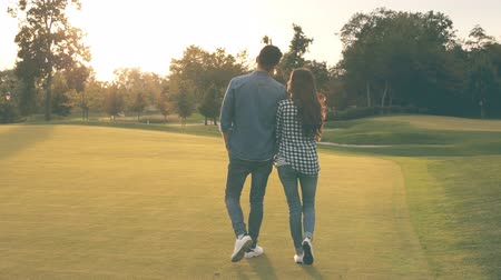 dátum : Couple holding hands and walking outdoors. Sunset time.