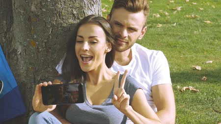Happy couple taking a picture of themselves with a smartphone on a green lawn. Slow motion. Dostupné videozáznamy