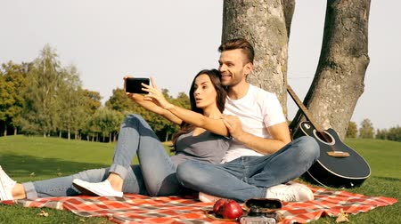 Happy couple taking a picture of themselves with a smartphone on a green lawn.