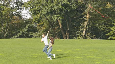 Happy couple flying on green lawn in the park. Slow motion. Dostupné videozáznamy