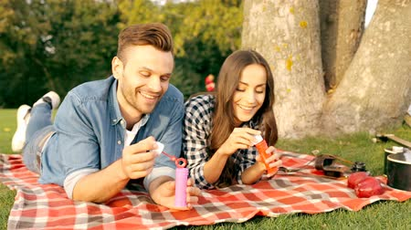 Happy couple blowing bubbles while sitting on tree