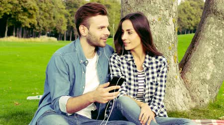 Happy couple is sitting under a tree and listening to music.