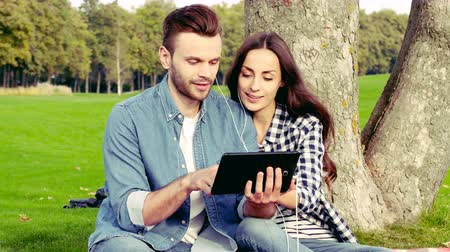 Happy couple listening music or watching video in the park.