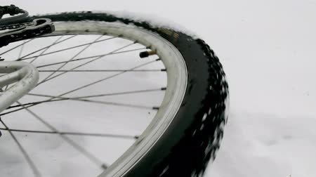 On this video you can see a bicycle wheel. Close up of a wheel of the bicycle. The bicycle in the winter wood lies on one side. Dostupné videozáznamy