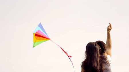 Happy couple flying a kite on a green lawn in the park.
