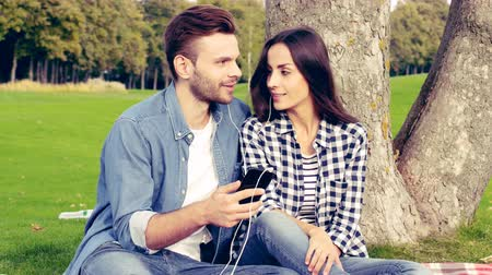 Happy couple lying under a tree and listening to music. Dostupné videozáznamy