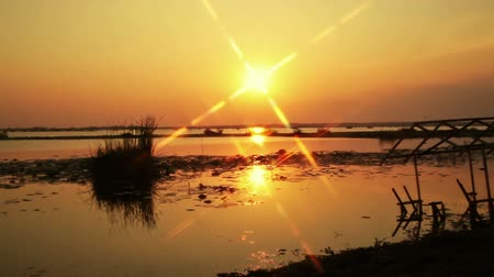 sel : sunset with flare star shape background, at river or lake and flood house on ground at twilight , camera panning shot