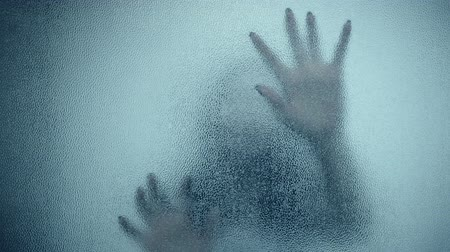 horror : female hand and head, spooky shadows on the glass wall, in full HD, Horror movie scene