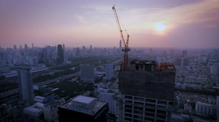 bakış : aerial top view at crane construction working and bangkok city area at twilight sunset, tilt down shot, High quality footage 4K Stok Video