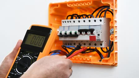 disjuntor : An electrician technician with a multimeter. Construction industry.