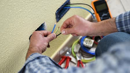 installer : Electrician technician worker prepare the electric cables of a residential electrical system. Construction industry. Building. Footage.