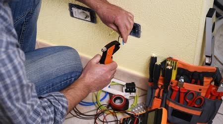 installer : Electrician technician worker with wire stripper Construction industry. Building. Footage.