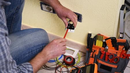 corrente : Electrician technician worker with screwdriver fixing electric cable to socket terminal in a residential electrical system. Construction industry. Building. Footage.