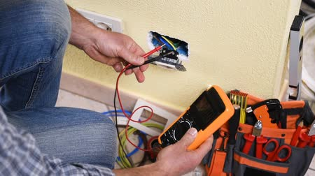 corrente : Electrician technician worker with multimeter it measures electrical voltage in a residential system. Construction industry. Building. Footage. Vídeos