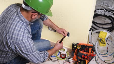 installer : Electrician technician worker preparing the electric cable in a residential electrical system. Construction industry. Building. Footage. Stock Footage