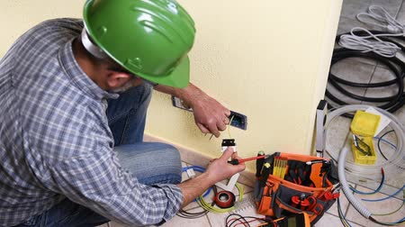 striptérka : Electrician technician worker with screwdriver fixing electric cable to socket terminal in a residential electrical system. Construction industry. Building. Footage.