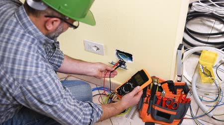 стриппер : Electrician technician worker with multimeter it measures electrical voltage in a residential system. Construction industry. Building. Footage. Стоковые видеозаписи