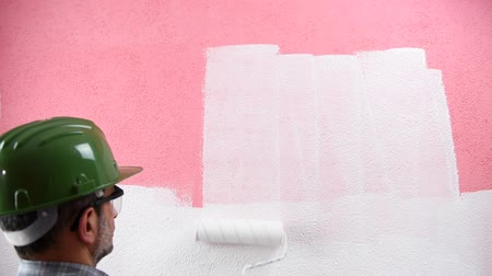 obnovit : Caucasian house painter worker in white overalls, with helmet and protective goggles. With the roller paints the pink wall with white paint. Construction industry. Footage.