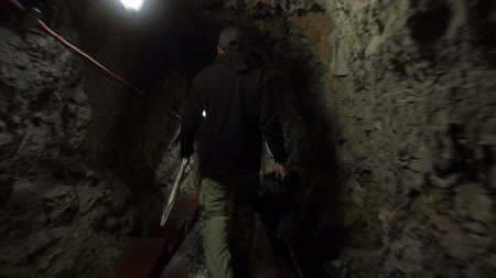 kazılmış : Man walks through dark rocky tunnel in Gibraltar.