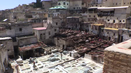 марокканский : Wide shot overlooking the tanneries of Fes, Morocco. Men working.