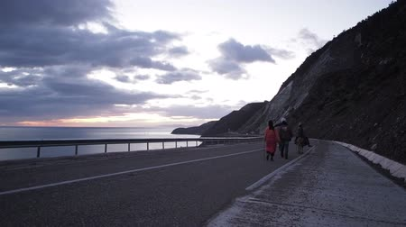 марокканский : Twilight off a coastal road near El Hoceima, Morocco. Family walks with their donkeys along the highway.