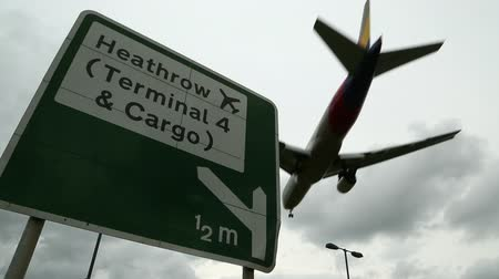 havai : Road sign for london heathrow airport with jet airliner flying overhead Stok Video