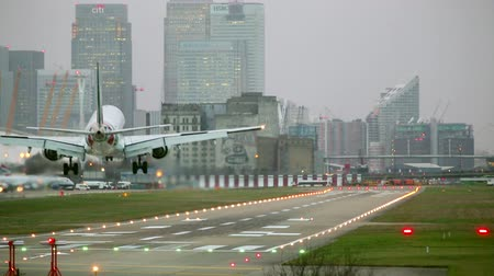docklands : A commercial airliner lands at London city airport with skyscrapers in the background.