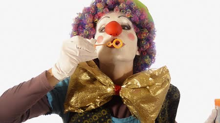 coringa : A sweet clown blowing soap bubbles on white background Stock Footage