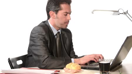 барахло : Businessman at laptop eating sandwich Стоковые видеозаписи