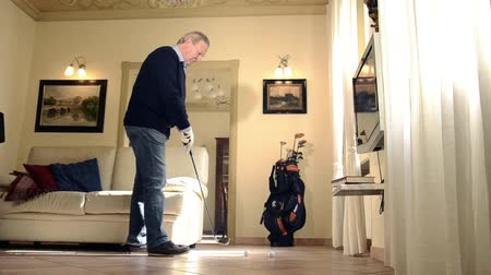cidadão idoso : Businessman relaxing at home, senior man practicing golf in living room Vídeos