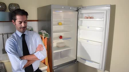 lodówka : disappointed man looking in his empty fridge