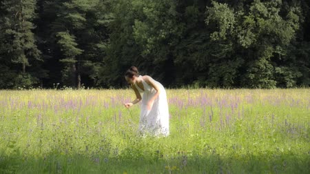 florido : beautiful girl in white walking on a flowery meadow Stock Footage
