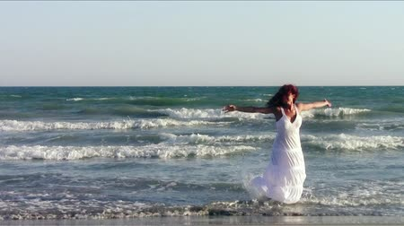 giydirmek : red-haired woman in white dancing on beach near the sea Stok Video